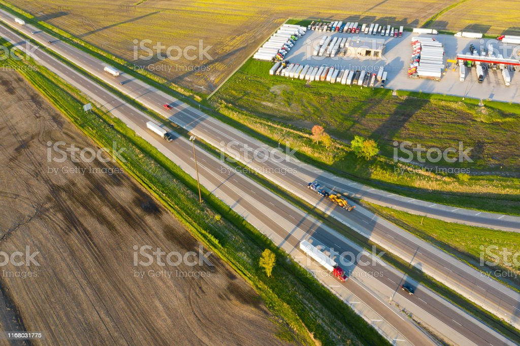 Multiple lane highway with traffic and a large truck stop with rows...