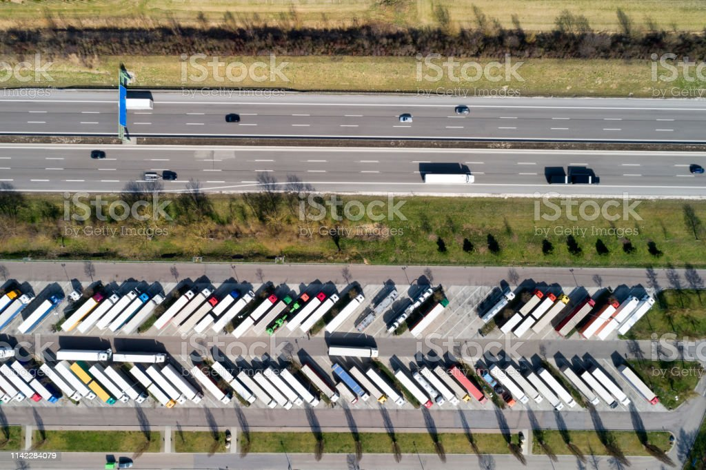 Highway And Truck Stop Full Of Semi Trucks Stock Photo - Download