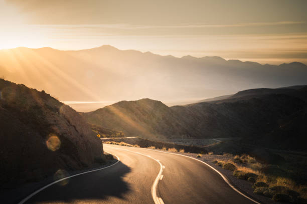 highway at sunrise, going into death valley national park - estrada imagens e fotografias de stock