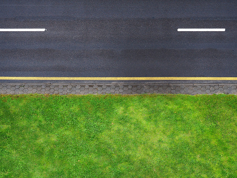 Highway background, roadside top view. Road view from above, black asphalt, white dividing strip, yellow stripe. Green roadside lawn, a pedestrian cobbled path