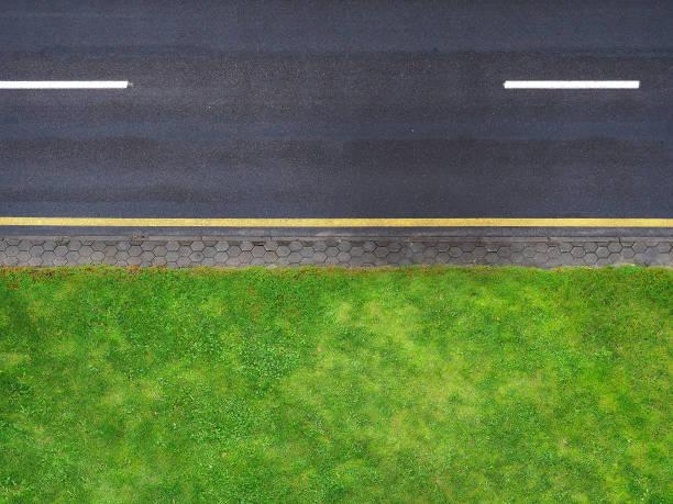 Fond de route, vue de dessus bord de la route. Vue route dessus, bande jaune noir asphalte, divisant la bande blanche. Pelouse de bord de la route verte, une voie piétonne pavée - Photo