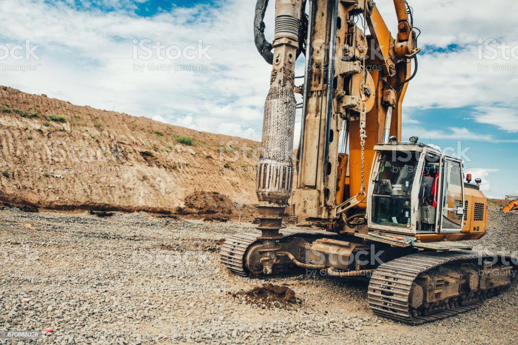 highway building with industrial rotary drilling machinery making holes in the ground stock photo