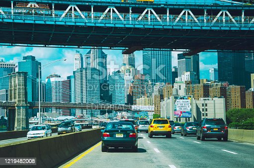 Aerial view looking at cars driving towards and under the Manhattan Bridge, in Manhattan, New York City, during a warm day in the summer.