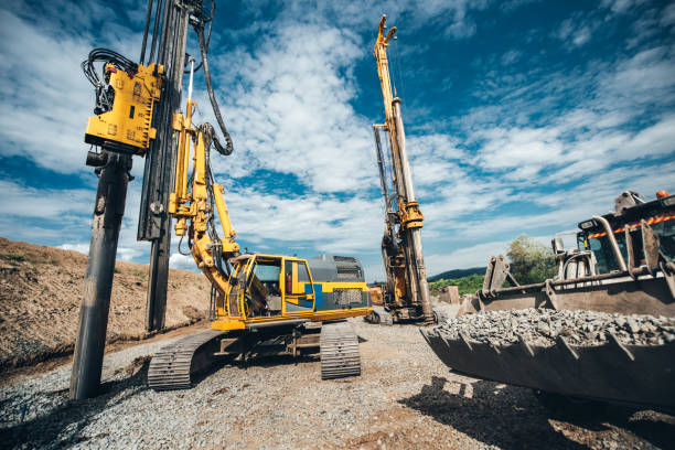 Highway construction site with heavy duty machinery. Two Rotary drills, bulldozer and excavator working Highway construction site with heavy duty machinery. Two Rotary drills, bulldozer and excavator working drill stock pictures, royalty-free photos & images