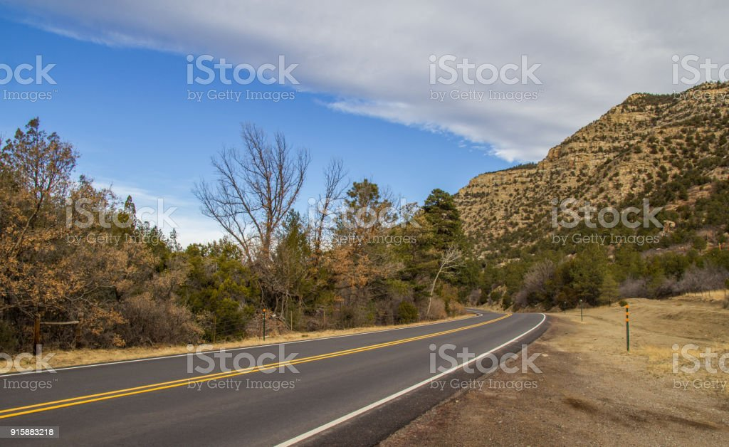 Highway disappearing around a rocky mountain stock photo