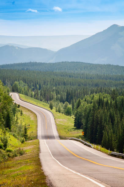 Highway disappears into Rocky Mountains stock photo