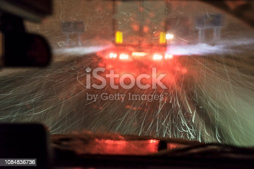 657042754 istock photo highway, driving at night during the blizzard 1084836736