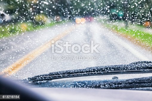 1054750504 istock photo Highway Driving POV Through Spattered Car Windshield During Rain Storm 613216154