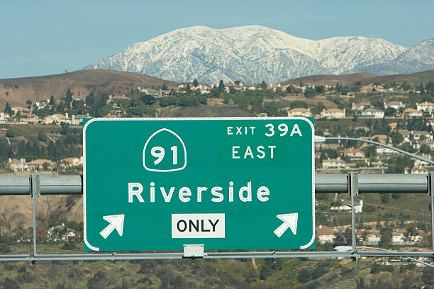Highway exit sign with mountains behind A highway sign taken on a winter day in Southern California. mount baldy stock pictures, royalty-free photos & images