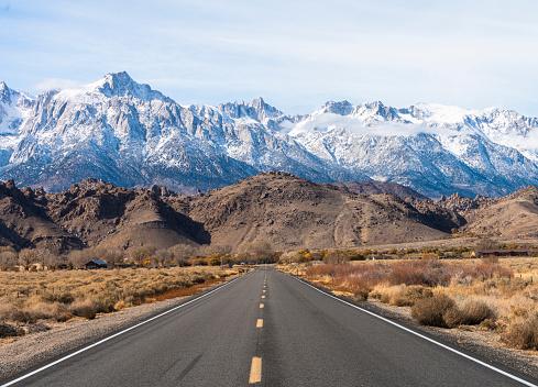 Highway heading toward Sierra Nevada mountains covered by snow.  California, USA