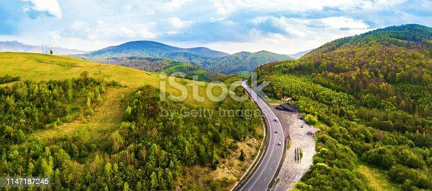 1042711480 istock photo Highway in mountains. Evening sunlight on hills. 1147187245