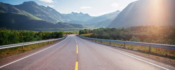 autopista en las montañas en las islas loften en noruega, hermoso paisaje, luz de la puesta de sol - vía fotografías e imágenes de stock