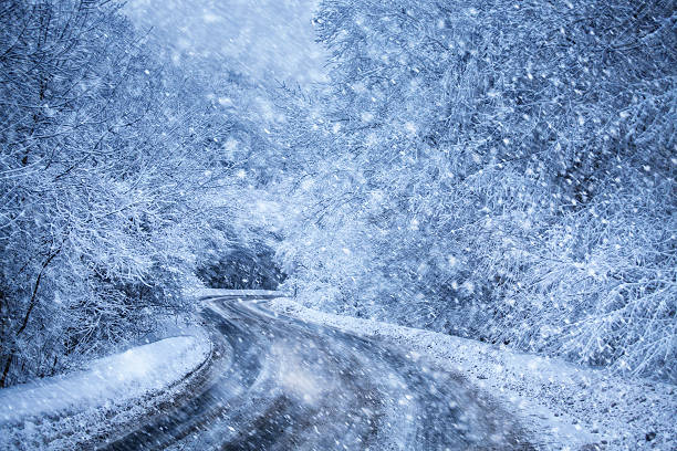 highway in the winter forest at snowfall stock photo