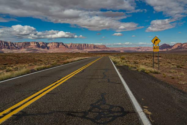 weg in de v.s. door de woestijn die tot rode bergen leidt - arizona highway signs stockfoto's en -beelden