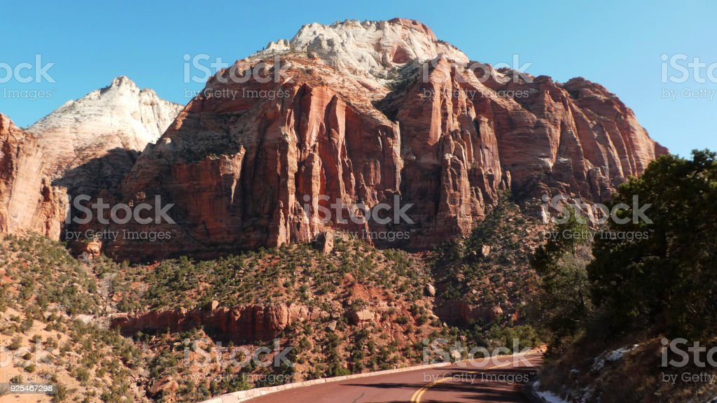 Highway in Zion National Park leading to tunnel to eastern entrance Utah below sandstone cliffs of East Sentinel Peak stock photo