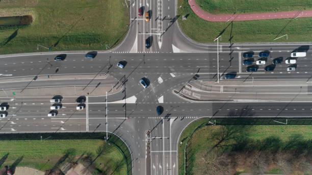 intersection de l'autoroute avec les voitures et les feux de circulation. vue de dessus de drone - carrefour photos et images de collection