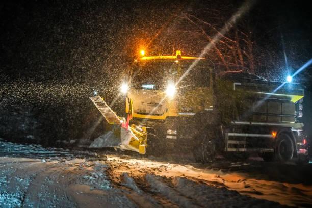 autobahn wartung lkw-reinigungsstraße während schweren schneesturm in der nacht, gefährliche fahrt während des winterverkehrs katastrophe. - dunkle flecken entferner stock-fotos und bilder