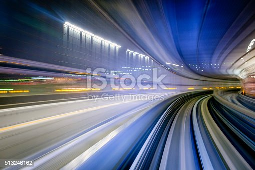 A motion-blurred view from the front of a train as it makes a corner at night in Tokyo, Japan.