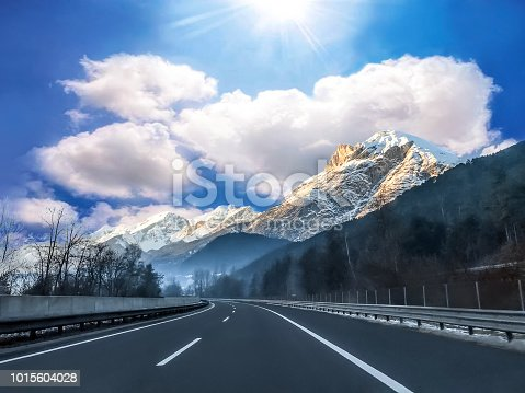 Highway on the background of snow capped Italian Alps. View of the mountain valley with asphalt road at sunrise
