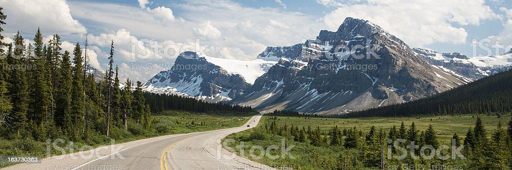 Highway passing below mountains stock photo