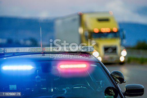 A patrol car with lights flashing is pulled off the shoulder to give a driver a ticket as a semi truck is driving by