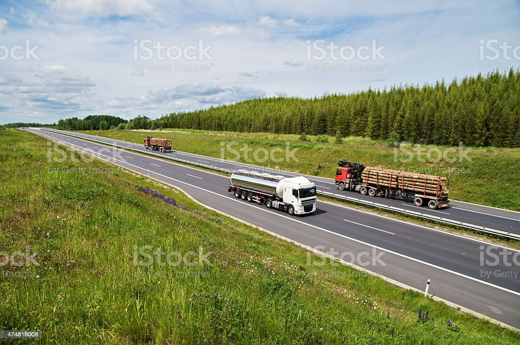 Highway rising flowering meadows. Tank and lorries transporting round timber. stock photo