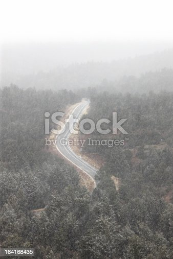 Heavy blizzard snow storm with fog descends upon a remote road through high desert juniper forest.  Sedona, Arizona, 2013.
