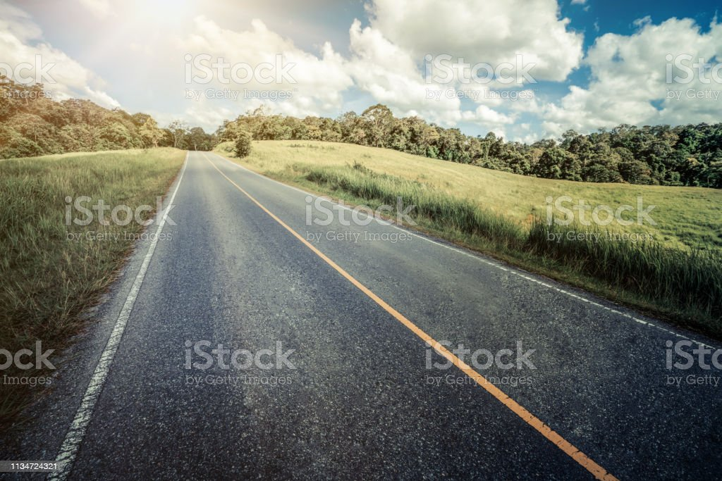 Highway road up hill through green grass field under white clouds on blue sky in summer day. Road trip travel concept. stock photo