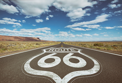 Highway sign for Route 66 on asphalt of country road