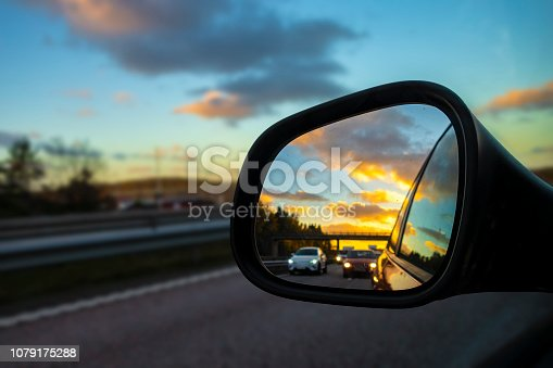Highway in rearview mirror during sunset