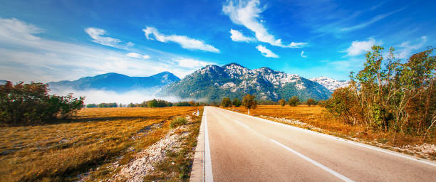 Highway through a desert landscape with mountains in background stock photo