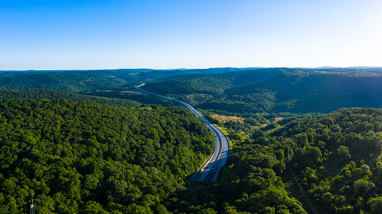 Aerial view of a two-lane highway winding through the Ozark mountains.