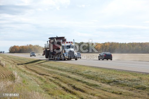 Dusty Highway in Agricultural territory.  Flatbed truck transporting Combine Harvest equipment.  Fields and farmland at side of highway.  Alberta.