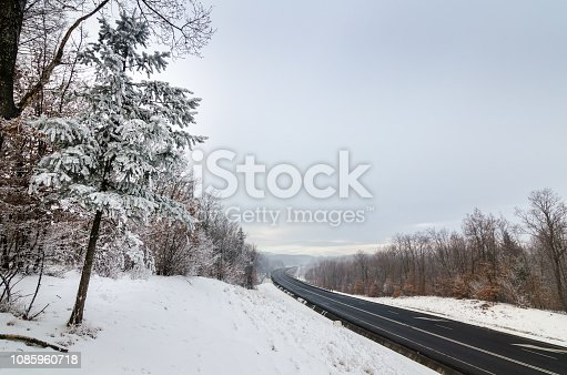 1066508460 istock photo Highway trough icy forest in winter season. 1085960718