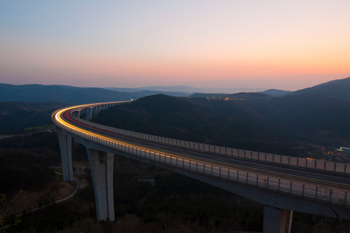 Long exposure landscape photo of highway viaduct, full of cars, at dusk. Crni Kal, Slovenia.