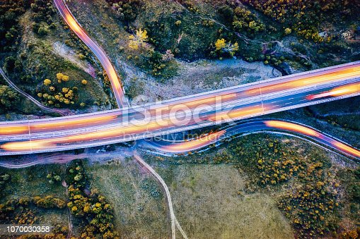 Aerial view of a highway and a curving country road with light trails