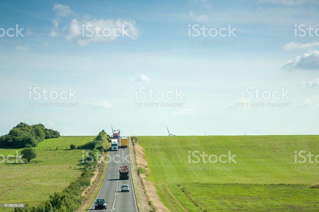 highway with cars, trucks green fields and windmill aerial - Foto de stock de Aerogenerador libre de derechos