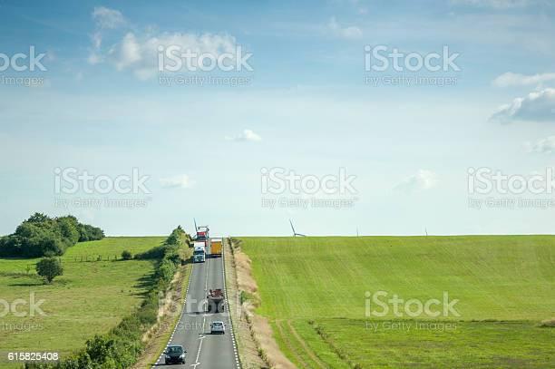 Highway With Cars Trucks Green Fields And Windmill Aerial Foto de stock y más banco de imágenes de Aerogenerador