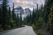 Highway with rocky mountains in pine forest at Moraine lake in Banff national park, Canada