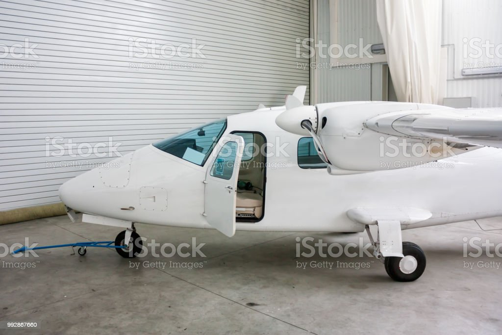 High-winged twin-engined light aircraft with open door in hangar стоковое фото