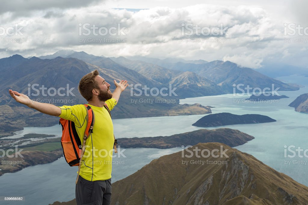 Young man hiker stands on a mountain top arms outstretched for...