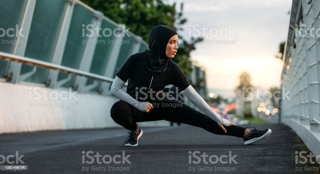 Hijab girl exercising outdoors in early morning - Foto stock royalty-free di Abbigliamento modesto