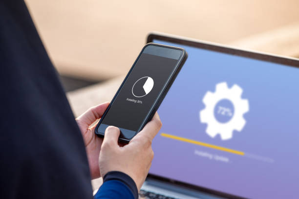 Hijab woman doing installing update on smartphone with installing upadate on screen laptop background stock photo