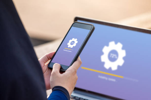 Hijab woman holding smartphone doing installing update process with gearbox percentage progress and loading bar with installing update on screen laptop background stock photo