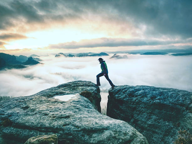 Hike in autumn mountains. Man stay above heavy mist in valley stock photo