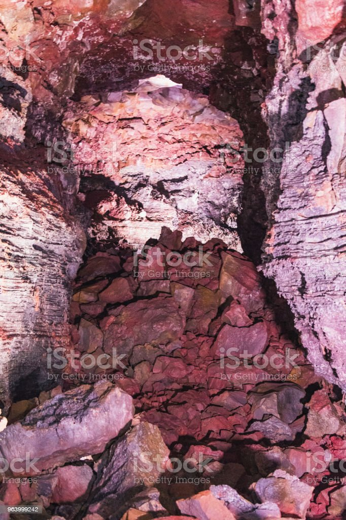 A hike through a lava cave in iceland tunnels are very narrow and partially blocked - Royalty-free Adventure Stock Photo
