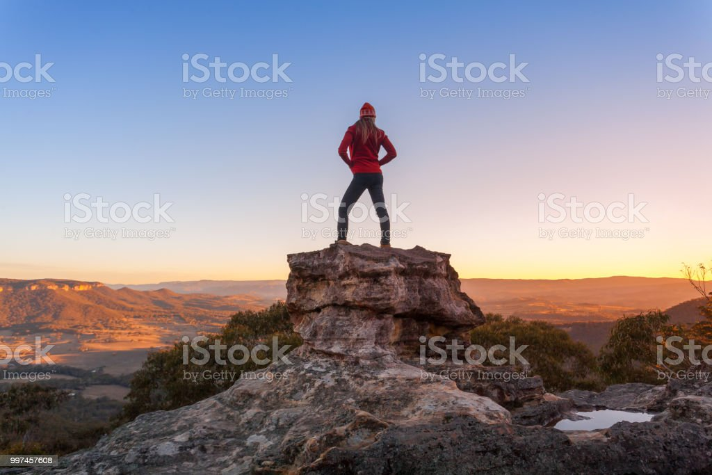 Female hiker standing on tall rock shaped pulpit with spectacular...