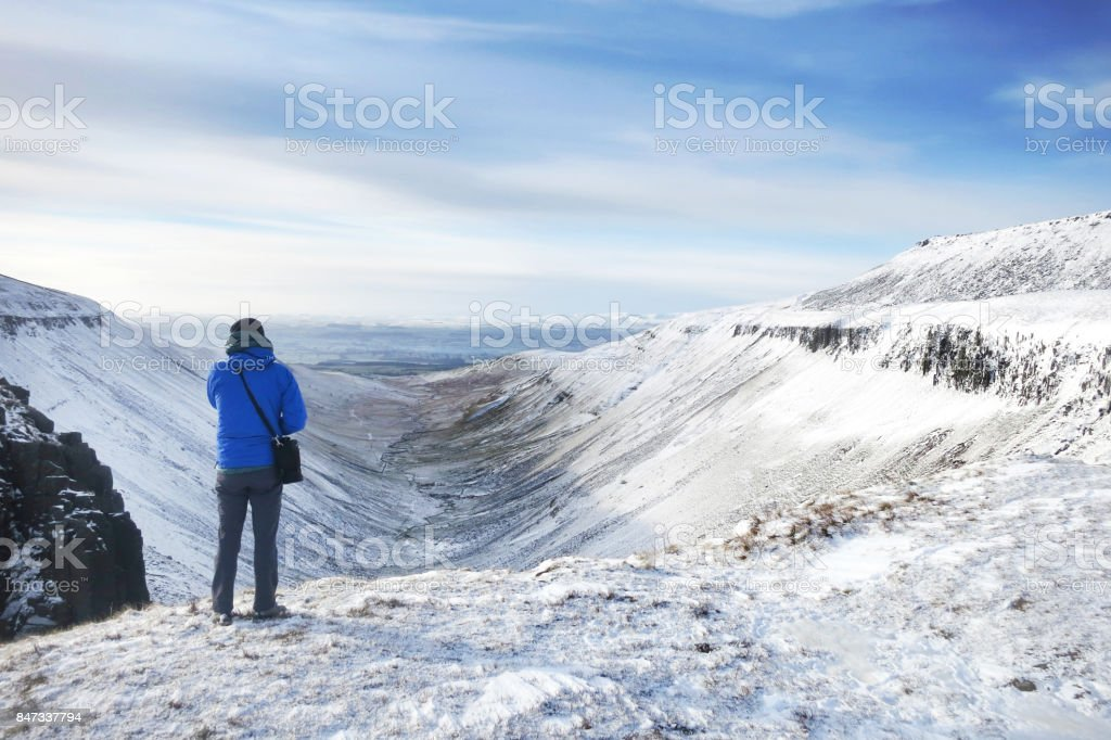 Hiker admiring the view of snowy landscape stock photo