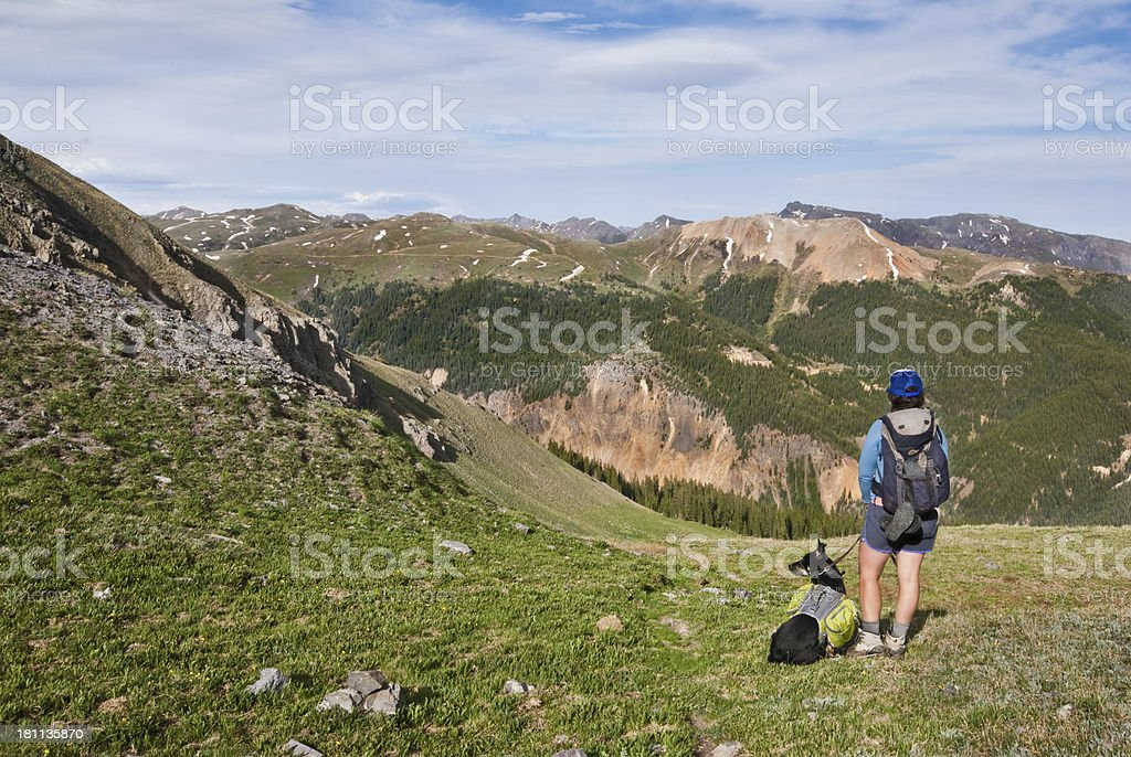 Hiker and Dog Looking at the View A young woman hiker and her companion dog look out over the San Juan Mountains from 12,000' Columbine Lake Pass in the San Juan National Forest near Silverton, Colorado, USA. Adult Stock Photo