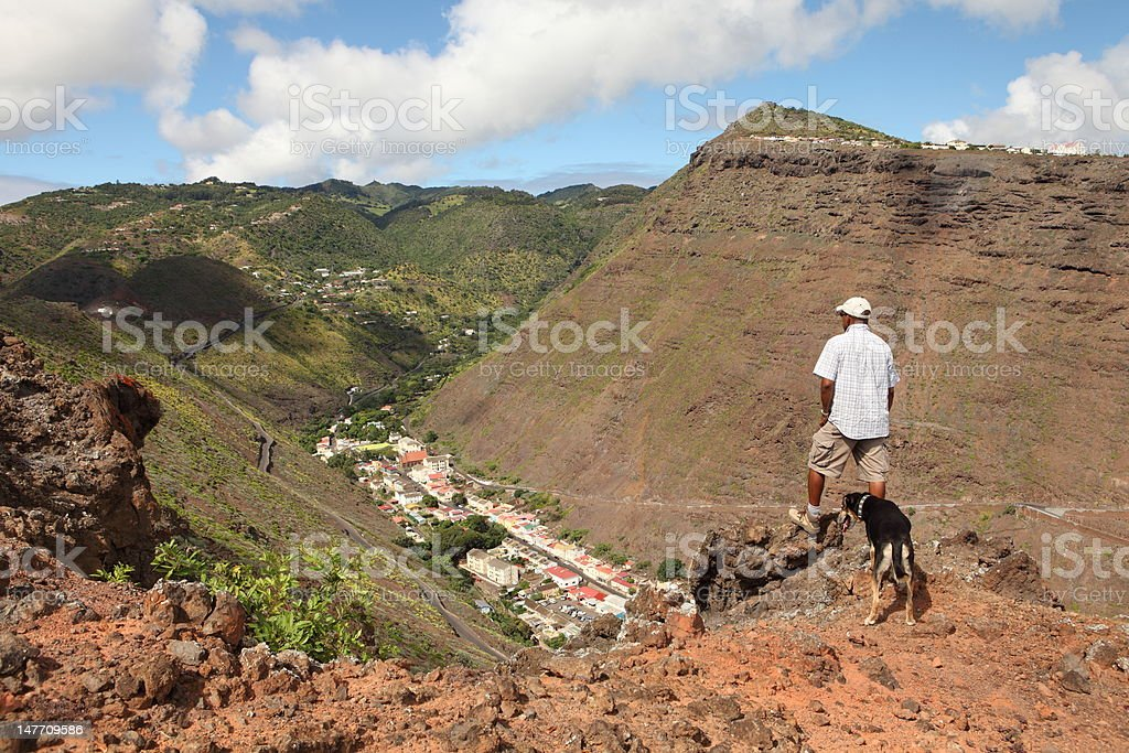 Hiker and dog on hillside above Jamestown St Helena Island stock photo